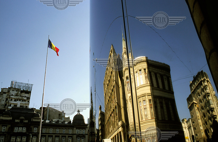 Romanian flag and reflection of buildings in a modern window.