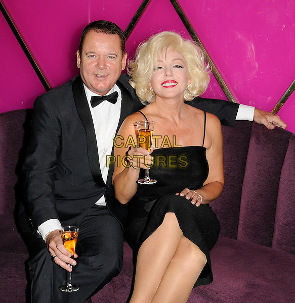 "LOUIS HOOVER & SUNNY THOMPSON .At the ""When Marilyn Met...Frank Sinatra, Dean Martin & Sammy Davis Jr."" photocall, Le Pigalle Club, Piccadilly, London, England, UK, .2nd September 2009..half length sitting at table re-creation scene lookalike lookalikes look-a-like glass of champagne drink black tux bow tie tuxedo dress .CAP/CAN.©Can Nguyen/Capital Pictures"