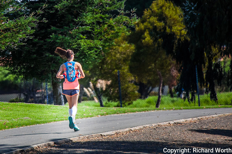 A young woman at the start of yet another training run, her pony tail swinging like a metronome.  And she is airborne, both feet in the air, as she begins a 20-mile run, preparing for a 26.2 marathon.