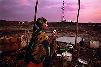 "Oil Field Refugee .A war refugee from the south tries to sell tea to oil workers.  The oil platform can be set up in 24 hours and is moved continuously south in a search for new oil fields...Story Summary:.Sudan, the largest country in Africa, hosts a civil war between the Islamic North and the African South that has the highest casualty rate of any war since World War II...Two and a half million people have been killed in this insidious conflict.  It drags on because Southerners have no voice, and the Northerners have engineered ""The Perfect War"" where none of their people are killed...The North forces people out of the South by bombing them, burning their crops, and harassing them with gunships. They abduct their children and draft them to fight with the Northern army--forcing southerners to fight their own brothers...This story is particularly interesting now because there is a small window for peace in a civil war that has been dragging on since the end of colonial rule.  The war has always been about tribal issues and ideology... but more than that, it is about resources.  This clash over resources may bring peace.  The North controls the pipeline and the only port, and the South controls the land...The story of Sudan has always been the continual transference of wealth from the resources of the south to the elite few who live in the deserts of the north.  And the sucking sound in the middle of the country is from the corrupt government in northern Khartoum.."