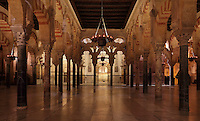 The hypostyle prayer hall, area built in the 10th century under Al-Hakam II, 961-976, with the mihrab in the distance, in the Cathedral-Great Mosque of Cordoba, in Cordoba, Andalusia, Southern Spain. The hall is filled with rows of columns topped with double arches in stripes of red brick and white stone. The first church built here by the Visigoths in the 7th century was split in half by the Moors, becoming half church, half mosque. In 784, the Great Mosque of Cordoba was begun in its place and developed over 200 years, but in 1236 it was converted into a catholic church, with a Renaissance cathedral nave built in the 16th century. The historic centre of Cordoba is listed as a UNESCO World Heritage Site. Picture by Manuel Cohen