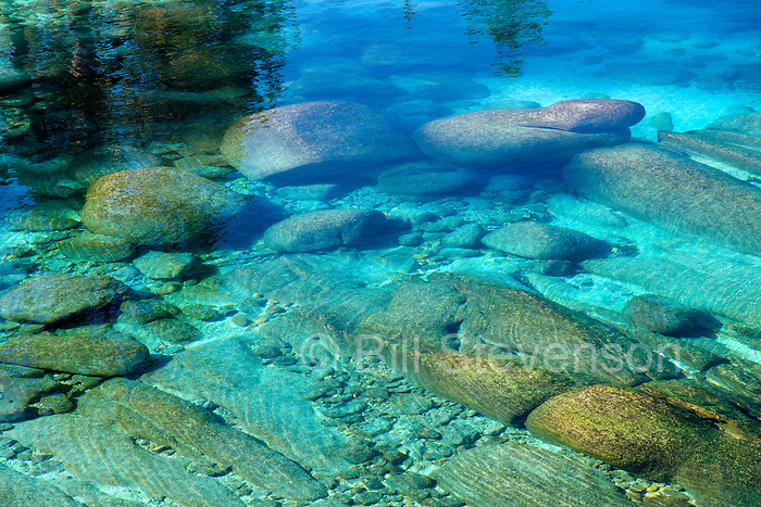 A photo of rocks beneath the clear blue water of Lake Tahoe. Lake Tahoe has a water clarity of about 70 feet. Tahoe is the 2nd deepest lake in the US and the 10th deepest in the world.