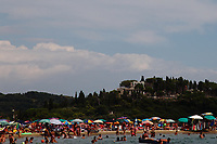 Scauri (Minturno): A view of the beach and of a part of the bay, that are crowded in the sunny summer day, by giving back the colorful atmosphere.  The hill on the background belongs to a small promontory that is a natural reserve. This is an enlargement of a part of the original photo.