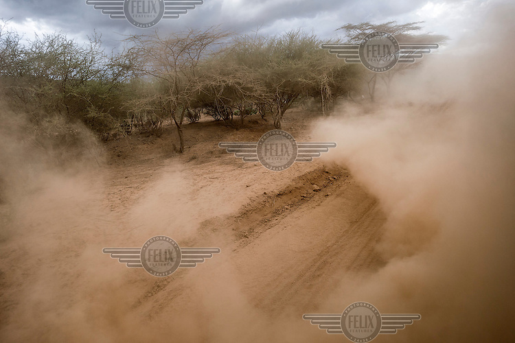 Dust thrown up by a vehcile travelling on an unpaved road.