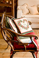 A salvaged chariot seat with hand-embroidered cushions in the living room