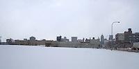 Detroit: paesaggio urbano invernale. Un campo ricoperto di neve dietro a cui si vedono palazzi e grattacieli.