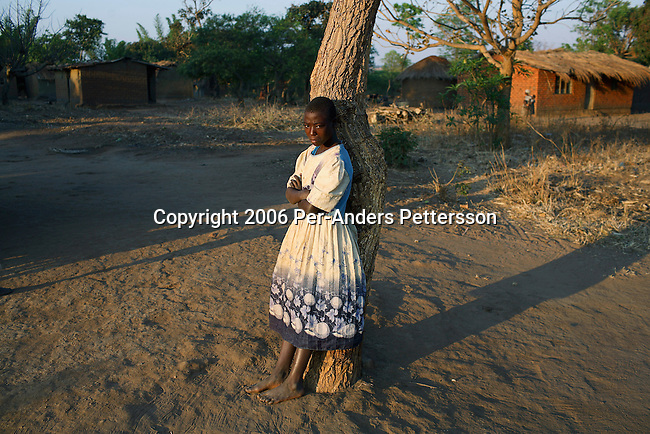 MPHANDULA, MALAWI - AUGUST 20: Mwaiwawo Mphandula age 13, stands outside the family house on August 20, 2006 in Mphandula village, about 30 miles outside Lilongwe, Malawi. She is one of the village chief's daughters. Mphandula is a poor village in Malawi, without electricity or clean water. Nobody owns a car or a mobile phone. Most people live on farming. About 7000 people reside in the village and the chief estimates that there are about five-hundred orphans. Many has been affected by HIV/Aids and many of the children are orphaned. A foundation started by Madonna has decided to build an orphan center in the village through Consol Homes, a Malawi based organization. Raising Malawi is investing about 3 million dollars in the project and Madonna is scheduled to visit the village in October 2006. Malawi is a small landlocked country in Southern Africa without any natural resources. Many people are affected by the Aids epidemic. Malawi is one of the poorest countries in the world and has about 1 million orphaned children. (Photo by Per-Anders Pettersson)