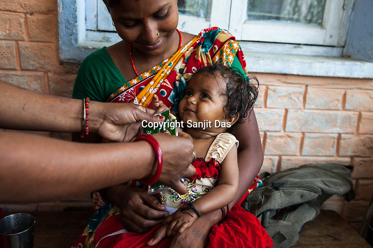 11 months old Sita is seen in a playful mood as the health worker feeds a dose of RUTF at the government health centre in  Hanuman Nagar, Saptari, Nepal.
