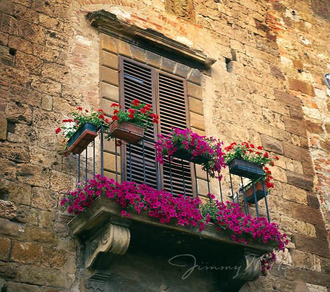 A balcony hangs on an old stone building in Italy