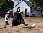 Father Joseph Pfeiffer of the St. Michael the Archangel Church in Farmingville playing soccer with students of a home study program during a break in a regular home-study gathering at the church on Monday October 3, 2005. (Photo by Jim Peppler.)