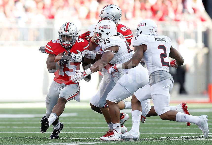 Ohio State Buckeyes running back Ezekiel Elliott (15) tries to get past Northern Illinois Huskies linebacker Boomer Mays (45) during the second half of the NCAA football game between the Ohio State Buckeyes and the Northern Illinois Huskies at Ohio Stadium on Saturday, September 19, 2015. (Columbus Dispatch photo by Jonathan Quilter)