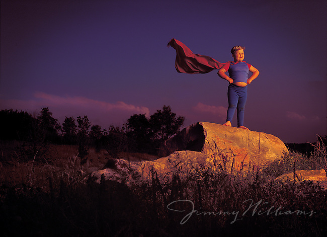 A young chubby boy dressed up as superman poses on a big rock in a field pretending to be a superhero.