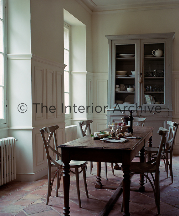 The large kitchen table is surrounded by simple painted bentwood chairs and an antique dresser arranged against the far wall houses a collection of glassware and crockery