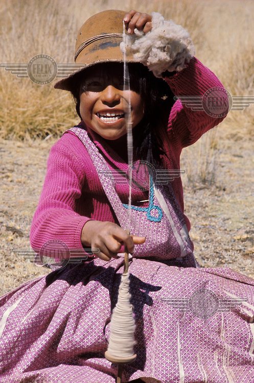 Aymara girl spins llama wool.