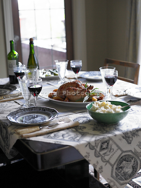 A table setting with Whole chicken roasted with apples, bowl of mashed potatoes, and red wine.