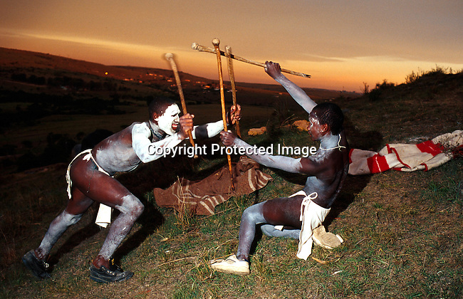 dicuinit00022 Culture Initiation Xhosa boys going trough the traditional manhood ceremony in Tshatshu, South Africa. An old tradition in making men out of boys in the Xhosa culture. These boys have been circumsised a week earlier. Two boys practicing traditional spear fighting, which in older generations was a way of getting prepared for battle against other tribes..The ceremony last for about 3-7 weeks, where they stay in huts in the bush removed from family and normal life. It starts with a circumsision and the wounds has to be healed in a natural way. They are guided by traditional healers and elders during the ceremony..©Per-Anders Pettersson/iAfrika Photos
