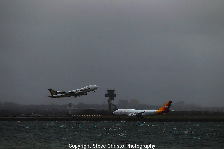 Bad weather and Coastal winds around Sydney Airport as a Singapore Airlines cargo plane takes off in front of an Air Pacific plane on the third runway at Botany Bay. Sydney Australia Monday 9th April 2013. Photo: (Steve Christo)