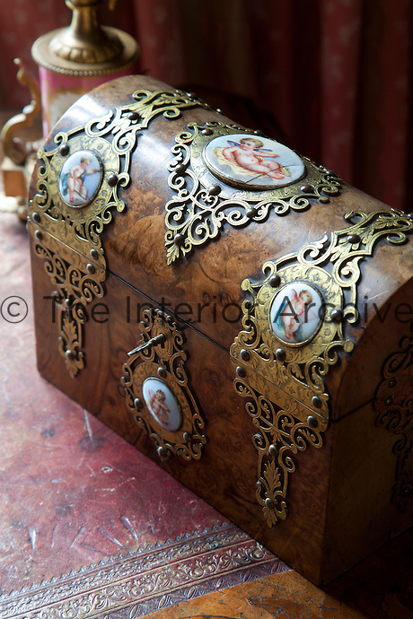 An antique walnut chest with enamel medallions featuring cherubs