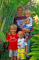 Two young children stand in front a smiling woman holding a small child in a garden at the Ronald McDonald House in Manoa, Oahu.