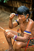 A-Ukre Village, Xingu, Brazil. Tikiri, an elder of the village, shaving his eyebrows with a disposable blue razor; Kayapo tribe.