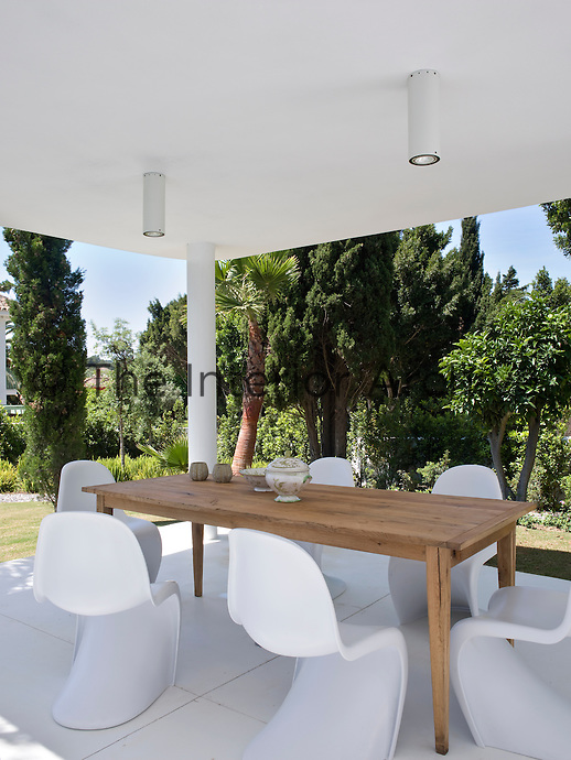A set of white Verner Panton dining chairs and a large wooden table create an outdoor dining room on the shady terrace