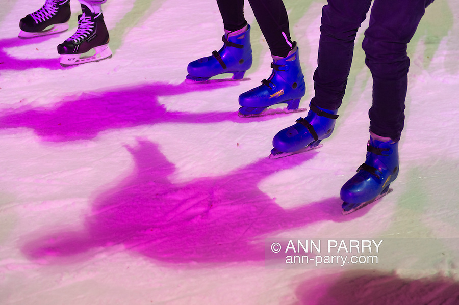 At Bryant Park's ice skating rink that night, skaters cast pink and green shadows on the ice. Manhattan, New York, USA. November 9, 2013.