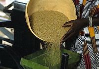 Woman throwing millet into the mill for processing