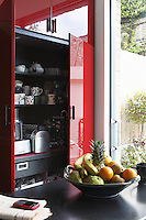 Full-height storage cupboards in the kitchen have been given a red high gloss finish