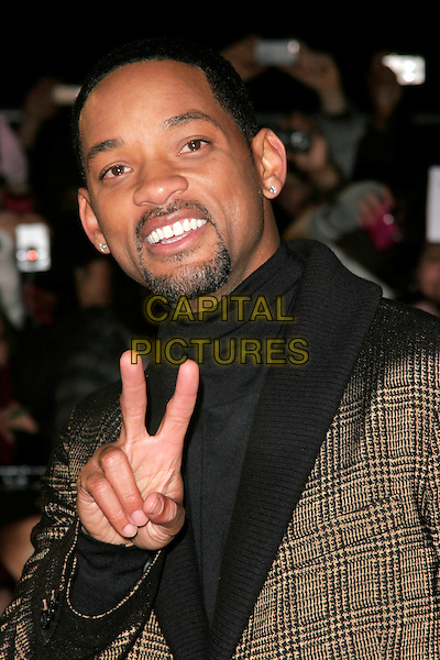 "WILL SMITH.The UK film premiere of ""Seven Pounds"" at the Empire Cinema, Leicester Square, London, England..January 14th 2009.half length hand v peace sign goatee facial hair  black polo neck jumper top earrings brown collar lapel plaid check checked jacket blazer.CAP/AH.©Adam Houghton/Capital Pictures."