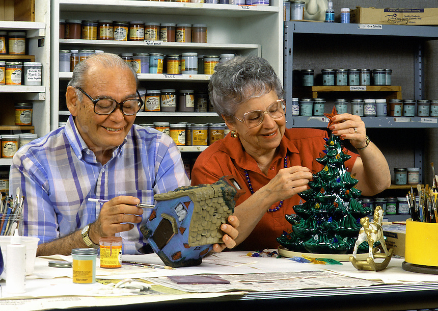 A smiling senior couple works on their ceramics products in an art class.