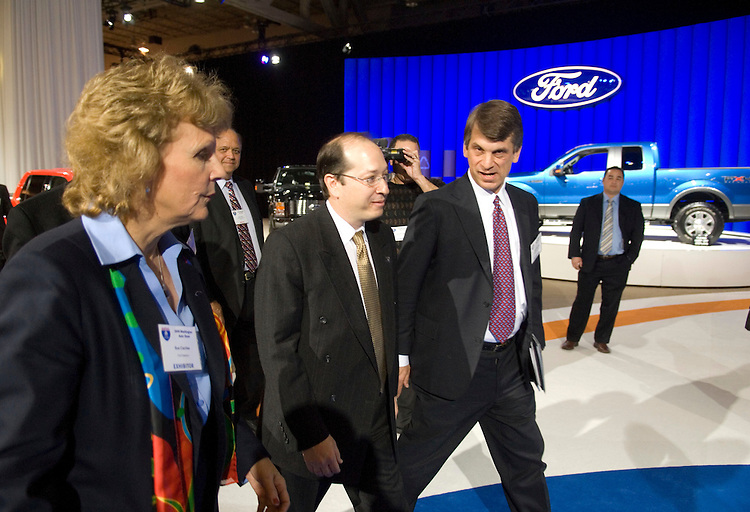"""WASHINGTON, DC - Jan. 22: Sue Cischke, senior vice president of Sustainability, Environment and Safety Engineering for Ford, Assistant Energy Secretary Alexander """"Andy"""" Karsner and David Sandalow, of the Brookings Institute, during media day at the Washington Auto Show. At left is a hybrid Escape, at middle background is a flex fuel F150; at right is a plug in hybrid Escape. (Photo by Scott J. Ferrell/Congressional Quarterly)"""