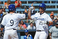 Asheville Tourists Bryce Massanari #25 is greeted at home after hitting a home run during a game against  the Lexington Legends at McCormick Field in Asheville,  North Carolina;  April 17, 2011. Lexington defeated Aheville 18-9.  Photo By Tony Farlow/Four Seam Images