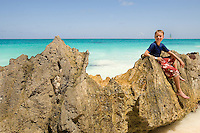 A young boy relaxes on a rock formation in the sandy beach and aqua water below the pre-Columbian Maya city, Tulum, near Cancun, Mexico. .