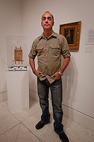 Cuban Artist Eduardo Miguel Abela Torras poses in front of his grandfather's works at The von Liebig Art Center, after the ribbon cutting ceremony to launch the 'Cuba on My Mind' exhibit, March 10, 2011. Photo by Debi Pittman Wilkey