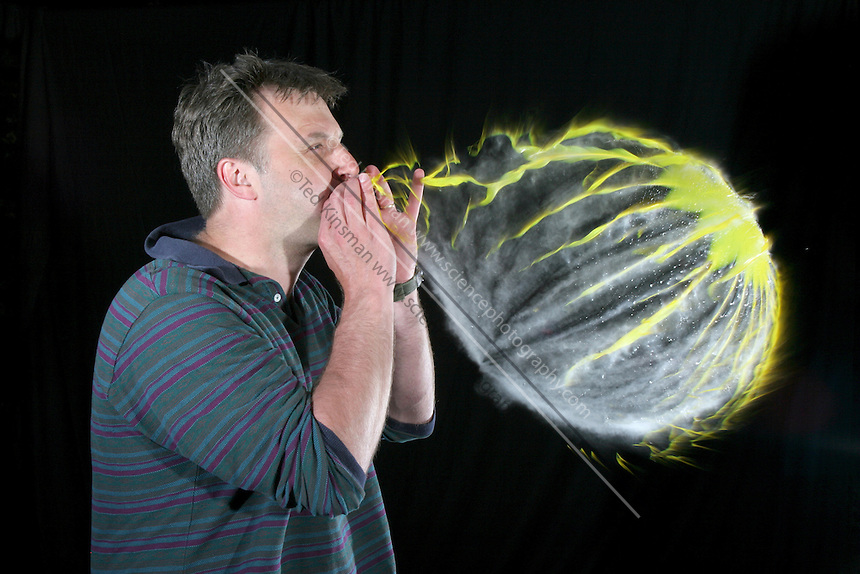 This image of a man over inflating a balloon was taken with a high speed flash system. The motion is effectively frozen in time due to the short duration of the flash (1/20,000 th of a second). The balloon was filled with a few milliliters of water before it was inflated. When the balloon is popped, the gas quickly expands and cools. This cooling converts the water vapor in the balloon into suspended water droplets which can be seen as a cloud.