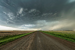 Dramatic storm clouds over a road leading into the distance, Saskatchewan.