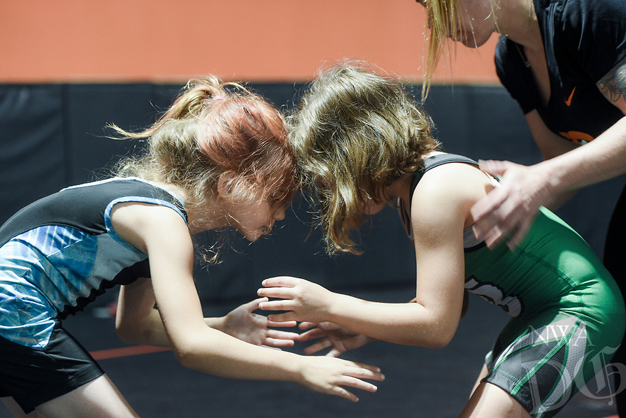 NWA Democrat-Gazette/CHARLIE KAIJO Eleora Robertson, 7, of Searcy and Teagen Loney, 7, of Van Buren (from left) wrestle with the help of coach Ashley Pagonis (right) during a women's wrestling camp, Monday, June 3, 2019 at the Honey Badger Wrestling Club in Bentonville<br />