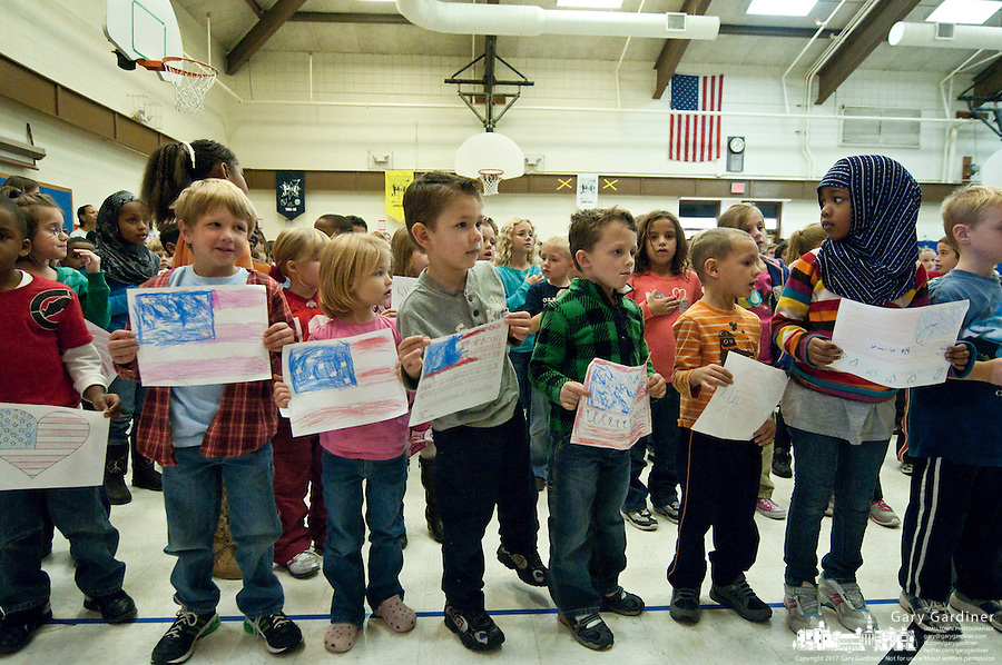 School children hold paper flags they created for observance of Veterans Day at Cherrington Elementary in Westerville, Ohio. The students gathered in the auditorium to listen to two U.S.Army soldiers talks about their experiences and presented gifts to the two men.