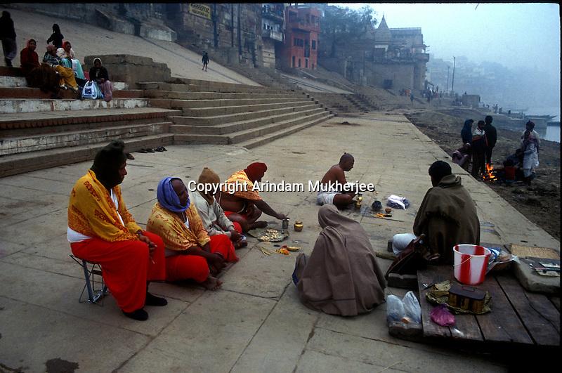 Indian men perfroms post death rituals at a ghat in Varanasi, Uttar Pradesh, India.