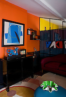 One wall of the bedroom is painted a vibrant orange giving maximum impact to the blue painting on the wall