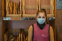 Interno di panetteria. La commessa con mascherina protettiva