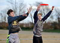 STAFF PHOTO BEN GOFF  @NWABenGoff -- 12/25/14 Jared Hines, 18, left, and Amos Yarbrough, 15, of Bentonville jump for a flying disc while playing with friends at Memorial Park in Bentonville on Thursday Dec. 25, 2014.