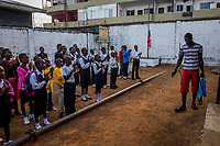 MONROVIA, LIBERIA - FEBRUARY 20: Humphrey, a caretaker, sprays the grounds with a concentrated chlorine solution, prior to the start of morning assembly on the fifth day of school, since schools closed due to the Ebola outbreak 6 months ago, at the C.D.B. King Elementary School on February 20, 2015 in Monrovia, Liberia. Though Ebola cases have receded into the single digits in Liberia, lingering fear and a depressed economy have dampened the turnout at schools. Many have yet to reopen, having failed to meet the minimum requirements put in place to prevent the transmission of the virus. Many of those that have reopened – like C.D.B. King, which, though located in the center of the capital, lacks electricity and running water, and has only a few toilet stalls for a student population that numbered 1,000 before Ebola — are struggling.<br /> Daniel Berehulak for The New York Times