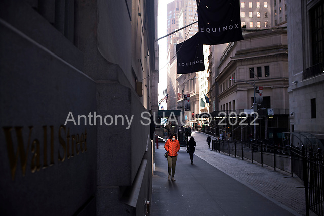 New York, New York<br /> March 18, 2020<br /> 9:18 AM<br /> <br /> Manhattan under coronavirus pandemic. <br /> <br /> The New York Stock Exchange and Wall Street void of people as the market falls over 10,000 points following weeks of the economic fear as a result of the virus. A woman walks by the NYSE wearing a mask in fear.