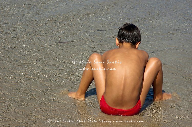Boy digging in the wet sand at Penguen Beach, Saint-Cast-le-Guildo, France.