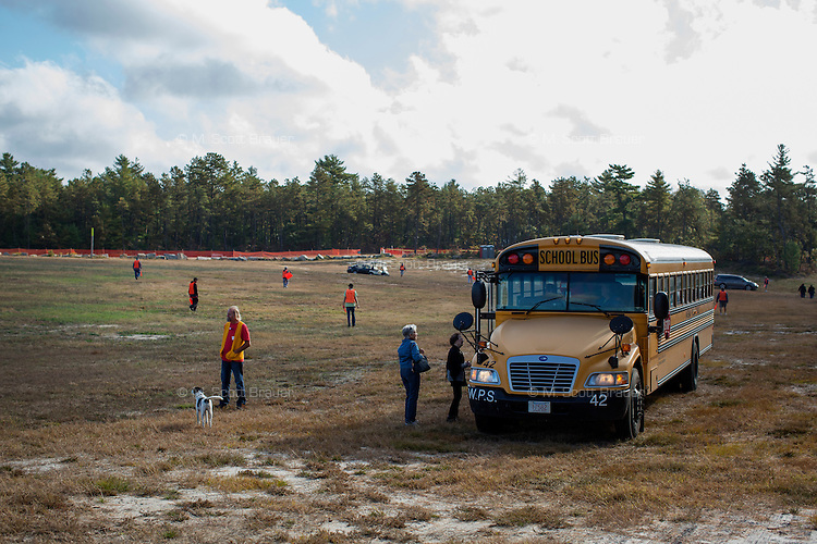 People get on a school bus to go to the AD Makepeace Company's 10th Annual Cranberry Harvest Celebration in Wareham, Massachusetts, USA. AD Makepeace is the world's largest producer of cranberries. These cranberries, wet harvested with varied colors, are destined for processing into juice, flavoring, canned goods and other processed foods.