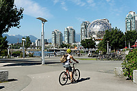 Young man riding bicycle with Telus World of Science dome in back at the Village on False Creek, Vancouver, British Columbia, Canada