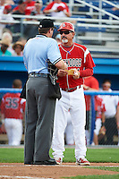 Batavia Muckdogs manager Dann Bilardello #11 makes a change with umpire Blake Carnahan during a NY-Penn League game against the Auburn Doubledays at Dwyer Stadium on September 3, 2012 in Batavia, New York.  Auburn defeated Batavia 5-3.  (Mike Janes/Four Seam Images)