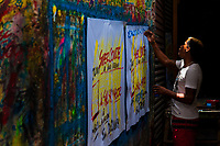 """A Colombian sign painter writes with a brush while working on music party posters in the sign painting workshop in Cartagena, Colombia, 16 April 2018. Hidden in the dark, narrow alleys of Bazurto market, a group of dozen young men gathered around José Corredor (""""Runner""""), the master painter, produce every day hundreds of hand-painted posters. Although the vast majority of the production is designed for a cheap visual promotion of popular Champeta music parties, held every weekend around the city, Runner and his apprentices also create other graphic design artworks, based on brush lettering technique. Using simple brushes and bright paints, the artisanal workshop keeps the traditional sign painting art alive."""