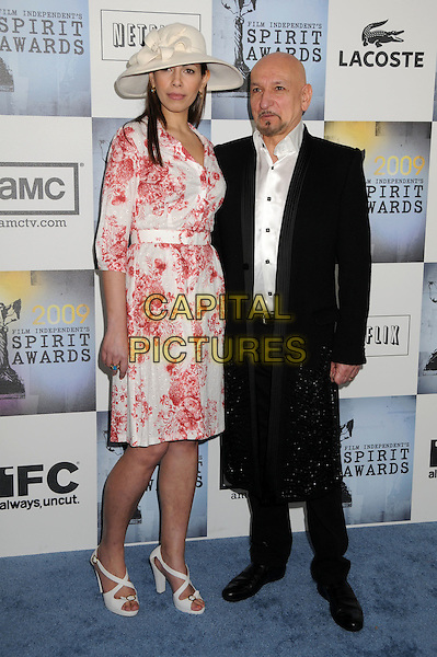 DANIELA BARBOSA DE CARNEIRO & SIR BEN KINGSLEY .2009 Film Independent's Spirit Awards - Arrivals held at the Santa Monica Pier, Santa Monica, CA, USA, .21st February 2009..indie independent full length hat white and red print dress summery white sandals shoes black suit husband wife long coat jacket .CAP/ADM/BP.©Byron Purvis/Admedia/Capital PIctures